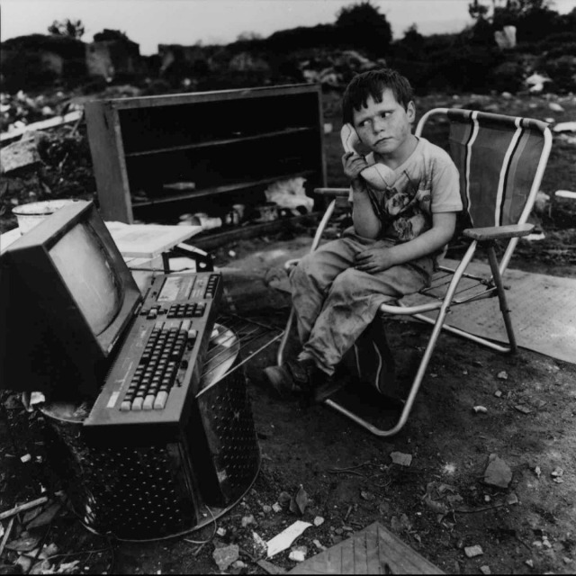 A little boy creates his own fantasy game amid his junky surroundings, in this photograph by Mary Ellen Mark,